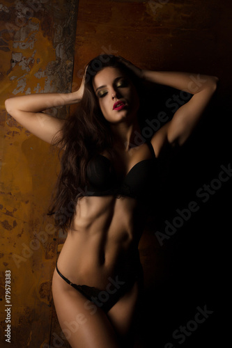 fototapeta na ścianę Sexy brunette model with long hair in black lingerie posing in the shadow