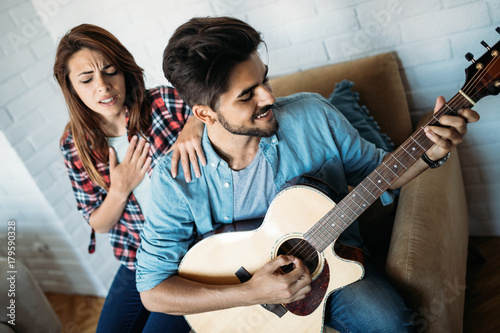 Young handsome man playing guitar while his girlfriend is singing Poster