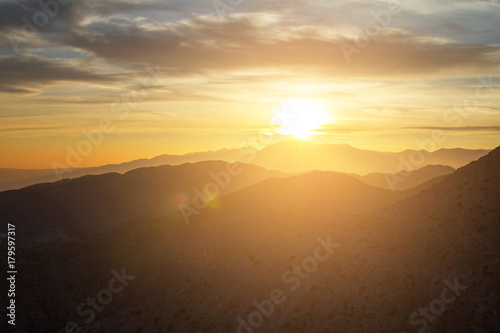 Glowing sunset view over the desert mountain landscape of Joshua Tree National Park in California