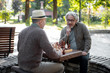 Thoughtful mature male pensioners entertaining with chessboard
