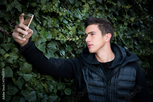 Handsome young man dressed in black, taking selfie with mobile smartphone outdoo Plakát