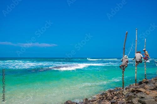 Fotobehang Tropical strand Fisherman stilt fishing beautiful Indian ocean