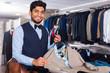 Man choosing jacket in shop