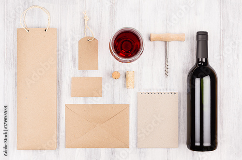 Corporate identity template for wine industry with bottle red wine and wineglass on soft white wood background. Mock up for branding, advertising, design, business presentations and portfolios.