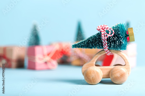 Miniature wooden car carrying a Christmas tree on a blue background
