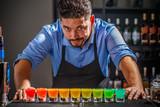 Barman with rainbow cocktai - 179667748