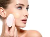 Girl applies  tonal foundation  on the face use sponge - 179667765