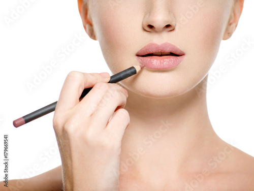 Girl apply lipstick with cosmetic pencil on the lips Poster