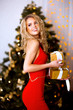 Portrait of Beautiful Woman in Lights. Fashion Dress and MakeUp. Christmas Santa. Elegant Lady in Red Dress over Christmas Tree Lights Background. Happy New Year.