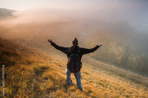 Man is hiking and enjoying sunrise in mountain. Poster