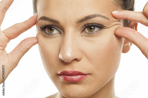 young women pinching her wrinkles  next to her eyes with her fingers