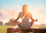 Woman yoga practicing and meditating on wooden in sunset outdoor background