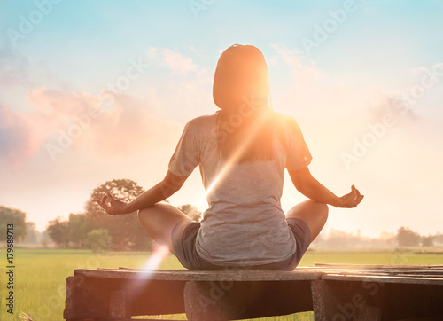 Fototapeta Woman yoga practicing and meditating on wooden in sunset outdoor background