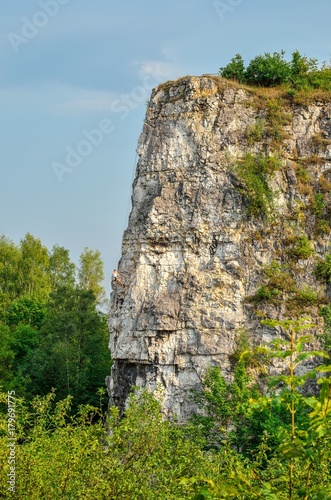 Beautiful summer landscape. Climber on the rocks of Twardowski at the lagoon of Zakrzowek in Krakow, Poland.