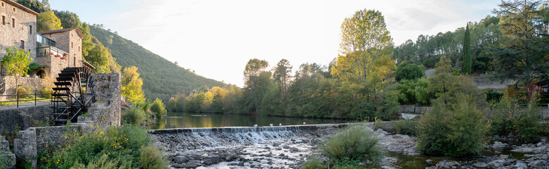 beautiful and colorful river mountain autumn fall season panoramic landscape with a watermill at sunset