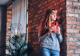 A woman drinks hot coffee near the wall of a red brick. - 179699772