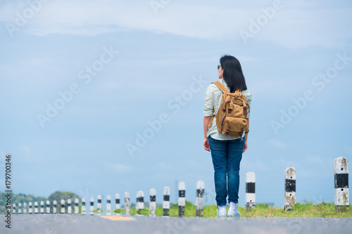 Traveler with backpack looking at blue sky,asia woman backpacker standing on road and looking forward to see way,freedom journey concept,hitchhiker travel Poster