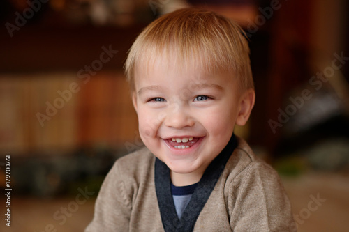 Little child near the fireplace with flowers Poster