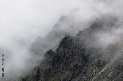 rugged mountain peaks in mist - 179703964
