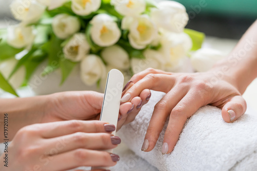 Foto op Canvas Manicure Close-up of the hands of a qualified manicurist filing the nails of a young woman