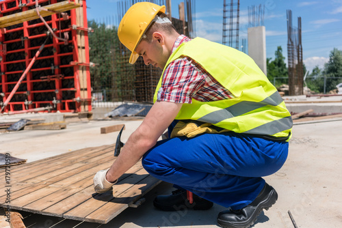 Side view of a young worker hammering a nail into wood during work on the construction site