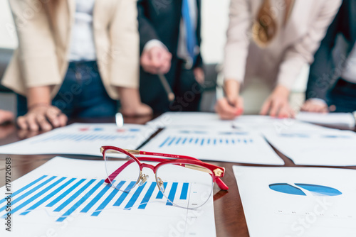 Sticker Close-up of eyeglasses on a printed bar chart showing progress during a meeting of business analysts