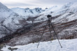 A DSLR camera on a tripod in front of a mountain view in the Yukon