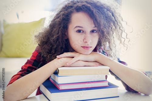 Teen girl resting on books