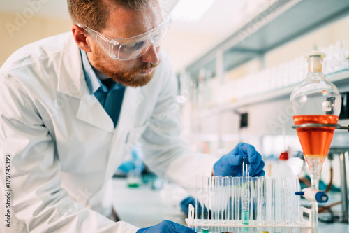 Handsome student of chemistry working in laboratory - 179745399
