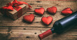 Valentines day. Red wine bottle, a gift and hearts on wooden background