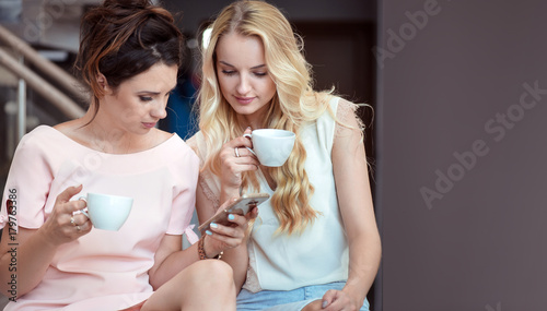 Foto op Canvas Artist KB Two relaxed girlfriends using a smartphone