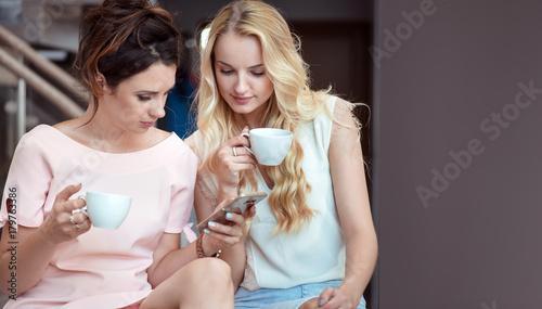 Plexiglas Konrad B. Two relaxed girlfriends using a smartphone