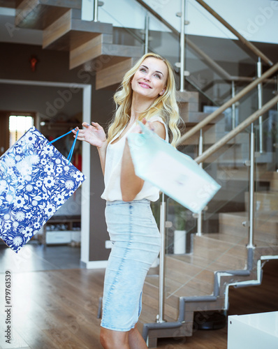 Foto op Canvas Artist KB Blond pretty woman holding shopping bags