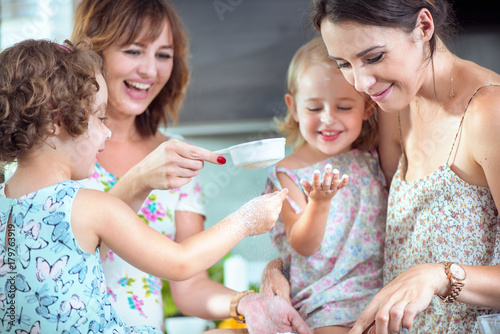 Deurstickers Artist KB Two mothers and their daughters baking a cake