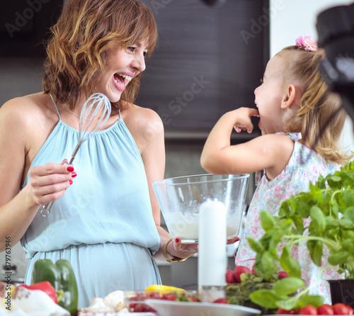 Plexiglas Konrad B. Mother and daughter preparing a tasty breakfast together