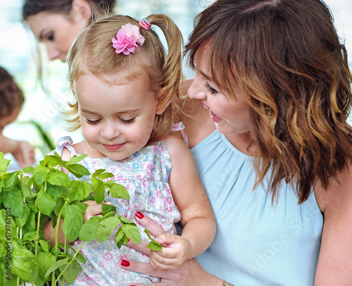Foto op Canvas Artist KB Mother showing her daughter the fresh herbs