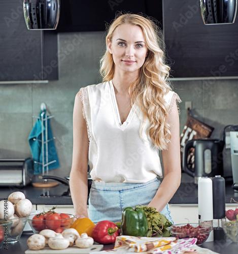Plexiglas Konrad B. Portrtait of a blond woman preparing a tasty dinner