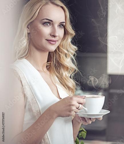 Plexiglas Konrad B. Portrait of a pretty blonde drinking a cup of coffee
