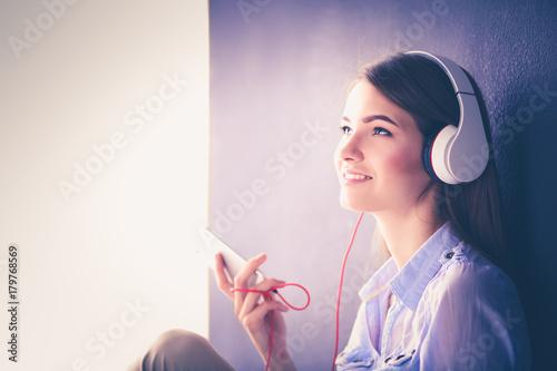 Fotobehang Muziek Woman listening music in headphones on windowsill background