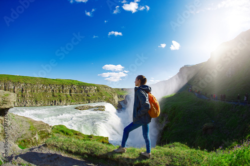Wall mural Girl in waterproof jacket and small orange backpack stands on the cliff on background of Gullfoss waterfall in Iceland. Travel to the Iceland