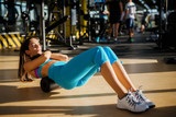 Beautiful active sporty young woman doing pilates on the floor with a foam roller in the sunny gym. - 179772949