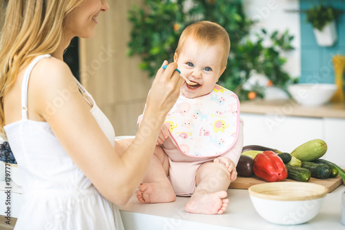 Mother Feeding Her Baby Girl with a Spoon Poster