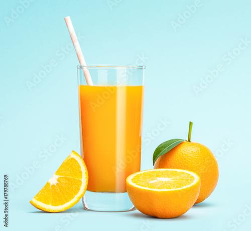 Fotobehang Sap Glass of fresh orange juice on wooden table, Fresh fruits Orange juice in glass with group of orange on blue background, Selective focus on glass
