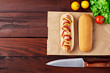Tasty Hot Dog with sausage, tomatoes, salad, and knife flat lay on wooden background. Top view.