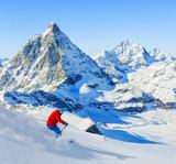 Man skiing on fresh powder snow with Matterhorn in background, Zermatt in Swiss Alps. - 179805573