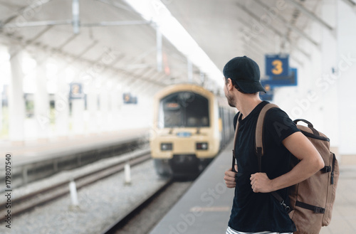 Young traveler walking with backpack on train staition and waiting train