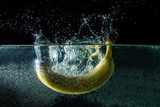 Banana falling in the water. Fresh Banana with a splash on the black background. banana gets hit by a water stream.