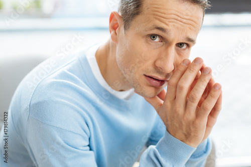 Sad look. Unhappy cheerless depressed man holding his chin and looking at you looking at you while having personal problems