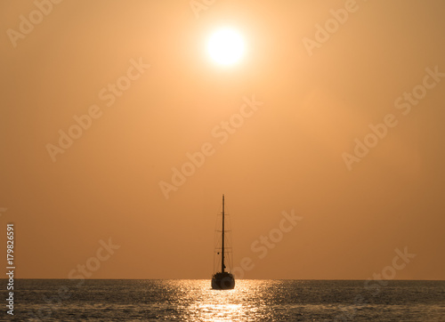Fotobehang Zee zonsondergang Yacht in the sea at sunset.
