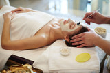 Side view portrait of beautiful young woman in SPA, lying on massage table with cosmetologist applying face mask to her skin